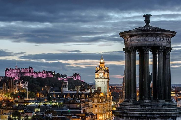 A view from Calton Hill over Edinburgh Castle illuminated by purple colours with, in the foreground, the famous memorial for the Scottish Philosopher Dungald Stewart. These monuments have a central position in the Scottish capital and are close to the old & new town. Restaurants nearby include the Whistle Stop Barber Shop, Zucca @ The Lyceum, Ciao Roma and Acanthus Restaurant.