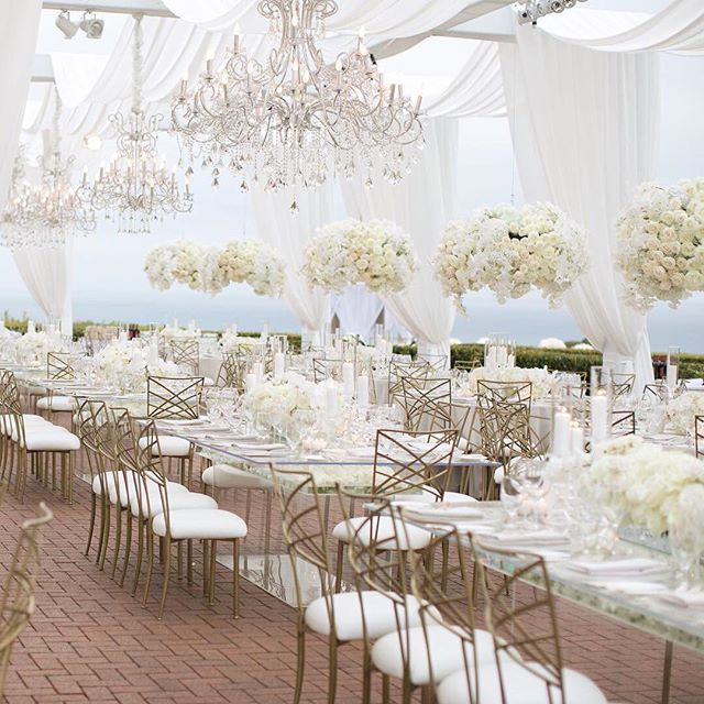 Want to make a statement with your decor? Hang chandeliers and floral arrangements from the ceiling to have your guests looking up in awe. ✨ #theknot  : @samuellippkestudios | Design and Decor: @whitelilacinc | Planning: @detailsalicia | Lighting: @shinelighting    #Regram via @theknot