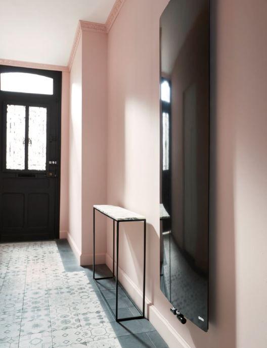 Dans cette entrée toute en longueur, la fraîcheur des murs peints en rose pastel fait ressortir les boiseries noirs et les carreaux de ciment du sol... et sublime le radiateur extra-plat installé là comme une oeuvre d'art.