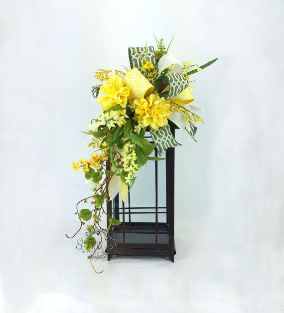 This Lantern Swag fits a 20-24 lantern and contains dahlias, wild flowers, greenery and a whimsical bow in the colors of yellow and green.