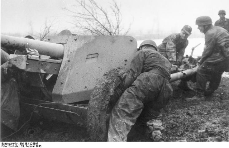 German paratroopers moving a 7.5 cm PaK 40 gun into position in muddy terrain, Italy, 23 Feb 1945