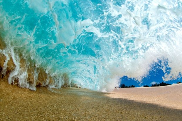 A large wave is captured laying on the dry sand as it throws over to create the shorebreak barrel in Oahu, Hawaii.
