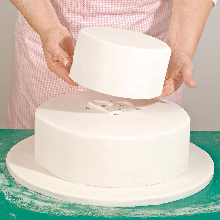 Wir zeigen bebildert Schritt für Schritt wie man eine mehrstöckige Hochzeitstorte übereinander stapeln kann und verraten hilfreiche Praxistipps.