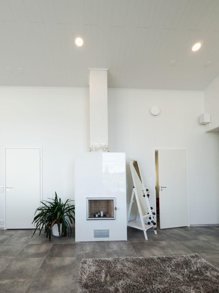 White fireplace with Lilja LED-lights shining on the ceiling. Valkoinen takka valaistuna Lilja LED-valoilla.
