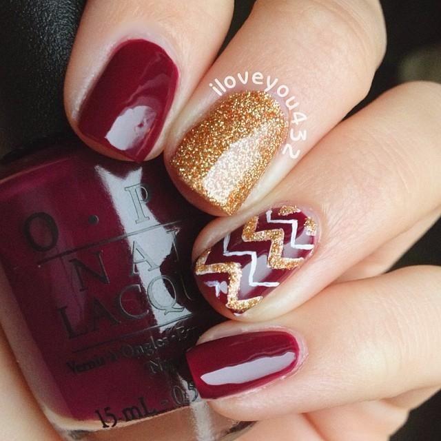 Burgundy and gold chevron nails.