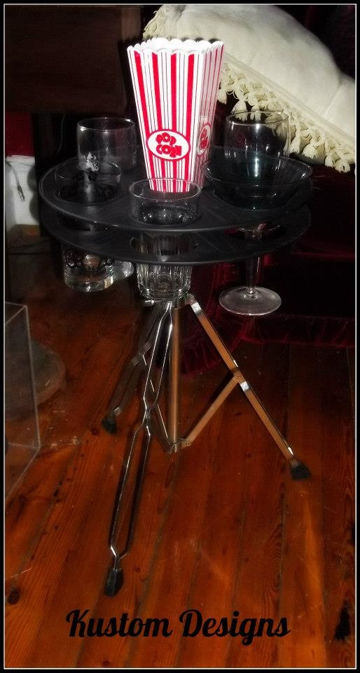 Metal antique film reel (1940's) sits on a repurposed snare drum stand to create this cinefile side table! Fits 6 glasses, has a center piece for snacks or to rest your beverage bottle.