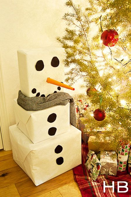 Christmas Gift Wrapping Ideas: White wrapping paper and black circles turn 3 plain boxes into an adorable snowman. You can make the circles out of black craft paper or felt. Roll orange craft paper into a pointed tube to make the nose.
