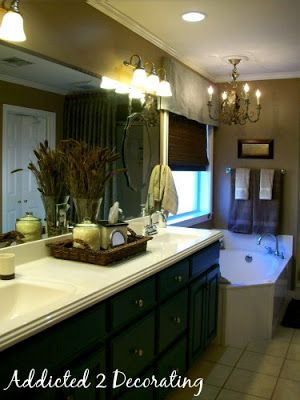 Master bathroom makeover--decorative mirrors added over plate glass mirror, accessories, chandelier over bathtub, valance, woven Roman shade