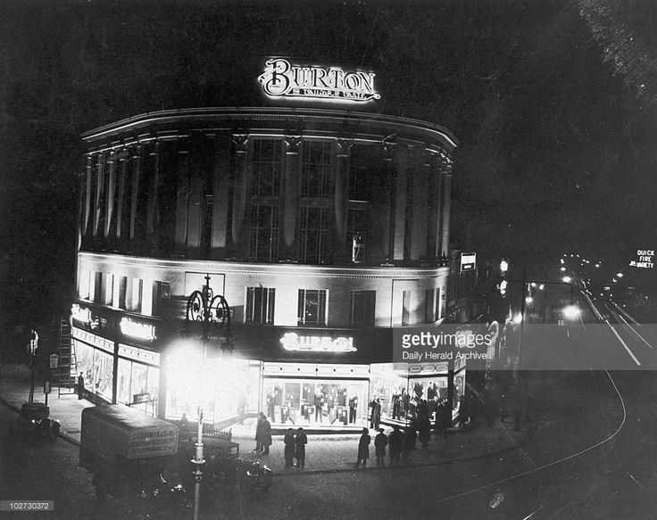 Burton store at night, Elephant and Castle, London, 9 February 1934. 'Floodlights on the wonderful new store which Montague Burton have built at the Elephant and Castle.' Photograph by George Woodbine.