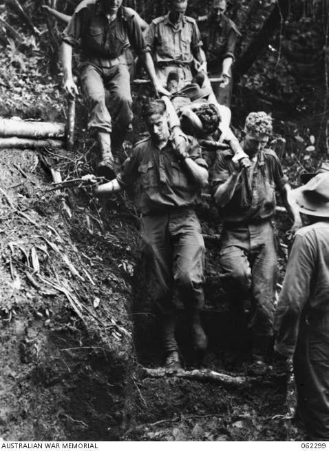 Identified left to right. Rear: Unidentified; VX91417 Captain J.C. ZWAR, Medical Officer, bearing stretcher; WX17091 Chaplain C.W.J. CUNNINGHAM, MBE (Roman Catholic). Unidentified injured personnel on stretcher. Front stretcher bearers: WX11750 Sergeant M. STEWART; WX32128 Private D.F. O'KEEFE.   Shaggy Ridge, New Guinea - 27th December