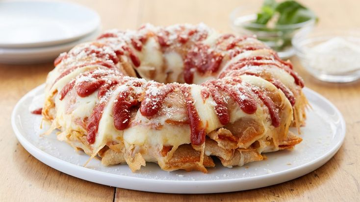 """Bundt cake gone savory with this fun spin on a monkey bread-style cheesy pizza roll cake. Topped with pizza sauce """"frosting"""" and Parmesan """"sugar,"""" pizza and bundt cake lovers alike will go wild for this one."""