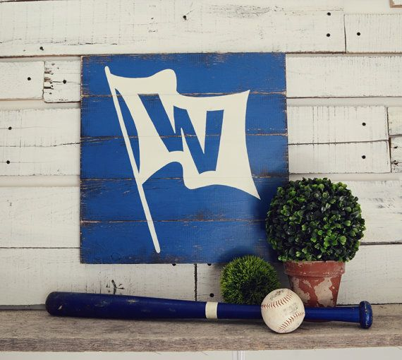 Bricks, ivy, and the waving W Flag. Support the Chicago Cubs like a true North Sider with this hand-painted ivory W flag on an aged and distressed blue slat background.  This item comes in different size options. Please select your desired size from the drop down menu.  A sawtooth hanger is included for hanging.  100% hand-painted. No vinyl.