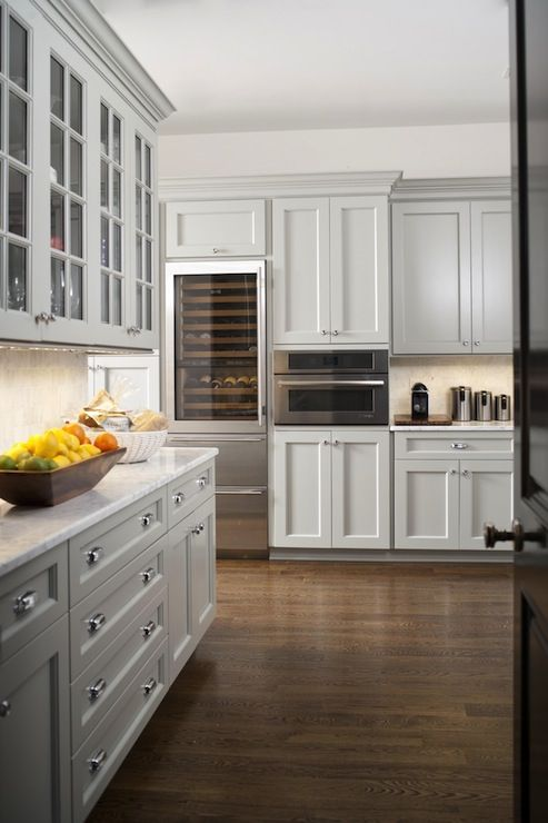 white marble countertops, white marble backsplash, glass front wine refrigerator, light gray cabinet
