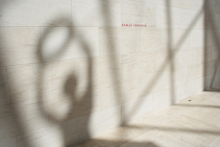 "Shadow of ""Lady Rosa of Luxembourg"" sculpture by Sanja Iveković on the walls of the Mudam Grand Hall"