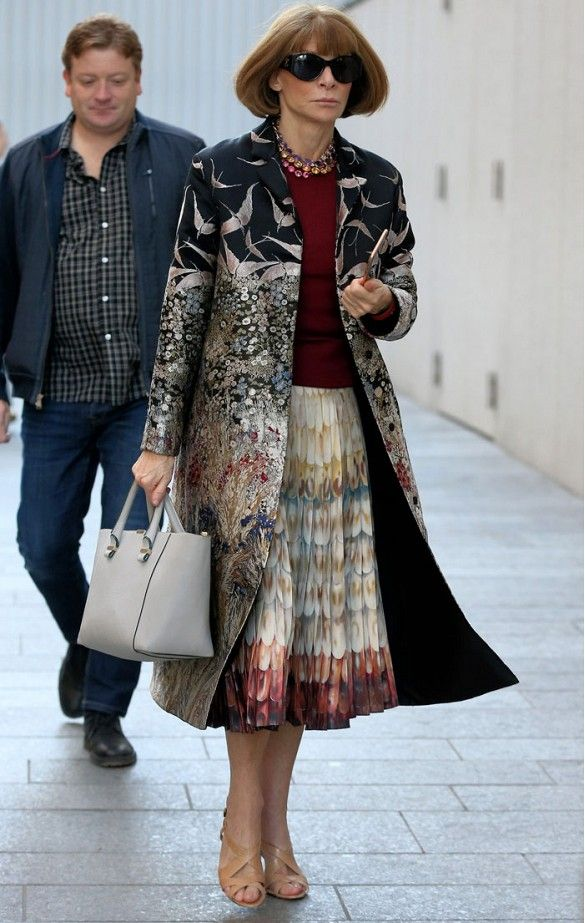 Anna Wintour wears a burgundy sweater, statement coat, printed skirt, satchel, and statement necklace