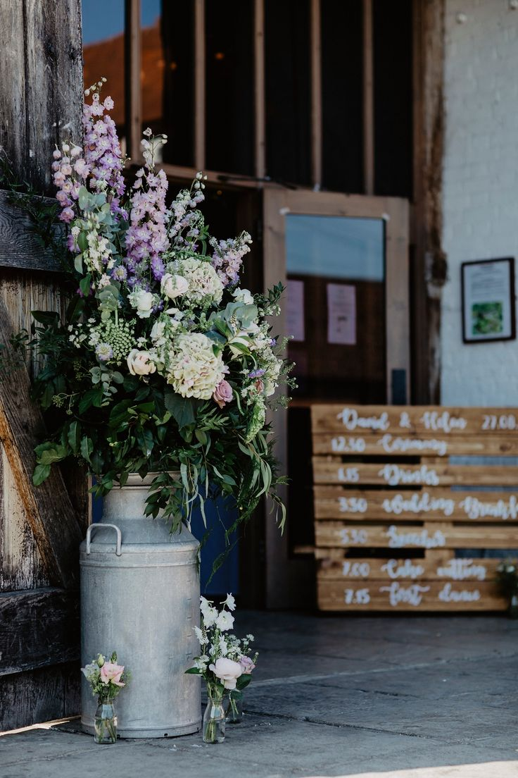 Milk churn filled with fresh flowers for a Rustic, Relaxed Wedding at Ufton Court. Images by  Benjamin Stuart Photography