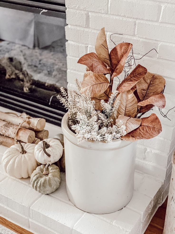 Decorating a neutral farmhouse fall fireplace hearth and mantle with a combination of faux florals in vintage crocks, green faux pumpkins, a large fall farmhouse sign, and neutral and earth tones create this cozy fall fireplace. Terracotta pots and vintage amber bottles, birch logs, cream throws and linen pillows create a cozy space by the fire. - Rain and Pine #farmhousedecor #falldecor #fallfarmhousedecor #fallcottagedecor #cottagedecor #fallcottagedecor #neutraldecor #cozydecor Fall Fireplace, Fireplace Hearth, Mantle, Fall Mantel Decorations, Thanksgiving Decorations, Holiday Decor, Fall Pillows, Linen Pillows, Fall Room Decor