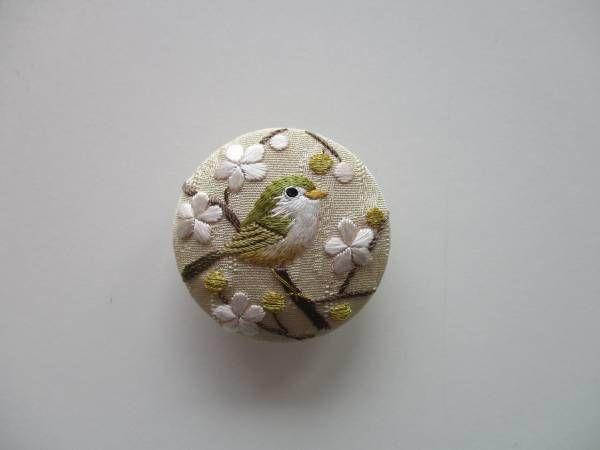 □商品詳細 日本刺繍の梅に鶯の帯留めです。 春告草と春告鳥として相性の良い組み合わせを、刺繍しました。 薄い黄色みのベージュ地(シャンパンのような色)の絹地を使用し、大きさは4cmの円形で、プラスチックのつつみボタンを土台としています。梅は生成りがかった白、梅のつぼみには金糸を使い、初春の華やかさを出しました。 存在感のある大きさで、つつみボタンのカーブと絹糸の光沢がきれいです。 □支払詳細 ・ゆうちょ銀行 ・みずほ銀行 ・三菱東京UFJ銀行 ・かんたん決済 □発送詳細 ・レターパックライト 360...