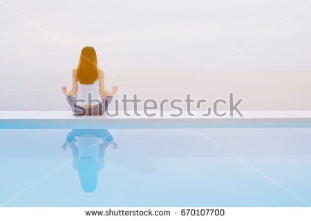 Asian adult woman sitting near the swimming pool and doing meditation with copy space, healthy and lifestyle concept