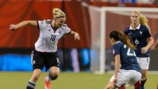 Alexandra Popp of Germany tries to move the ball past Amel Majri of France