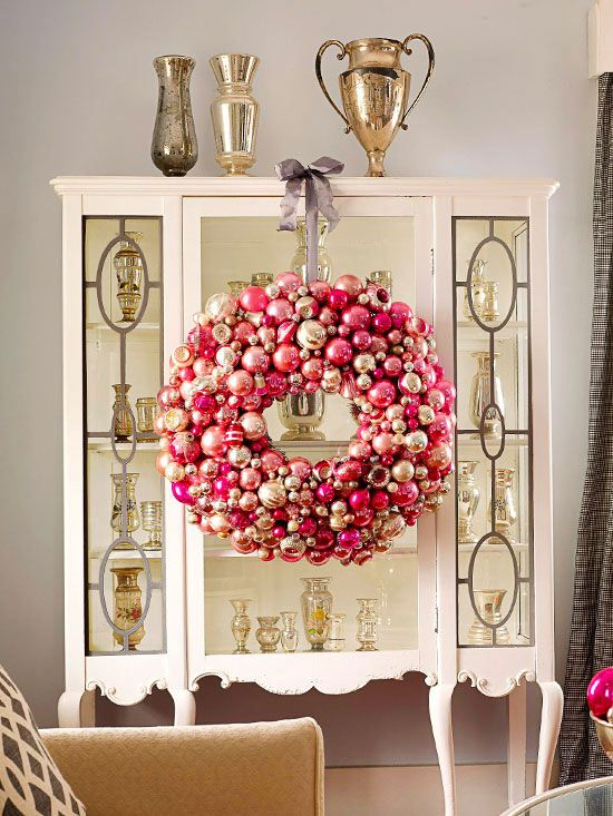 Love the idea of hanging a fun colored glass ornament wreath to a display case.