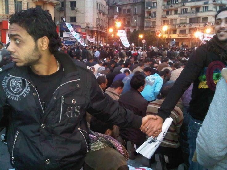 Cristiani proteggono i musulmani durante la preghiera nel mezzo dei moti del 2011 a Il Cairo, Egitto