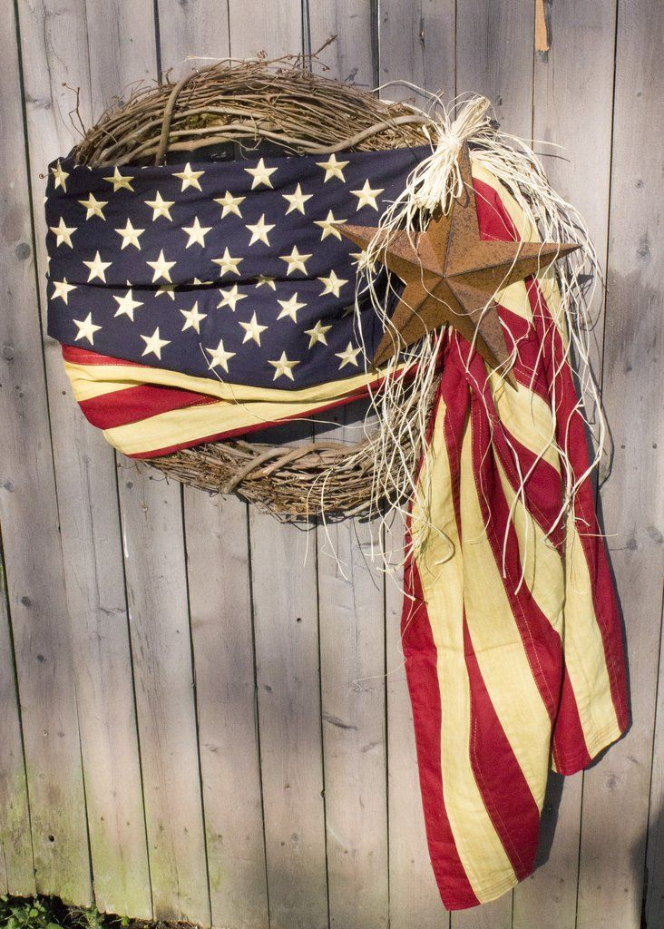 """This American Flag wreath is 24"""" created out of grape vine, the flag is tea-stained to add a bit of old world's charm, and also included is a 12"""" rusty tin star accented with a bit of raffia and angel"""