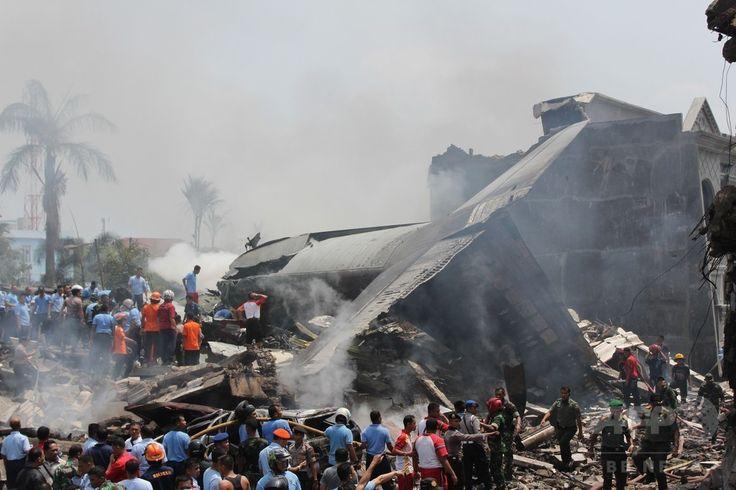 インドネシア・スマトラ島、メダンの住宅地に墜落したインドネシア軍の輸送機ハーキュリーズの残がいの周りに集まる群衆(2015年6月30日撮影)。(c)AFP/Kharisma TARIGAN ▼30Jun2015AFP|住宅街に軍輸送機墜落、死者110人超の恐れ インドネシア http://www.afpbb.com/articles/-/3053212