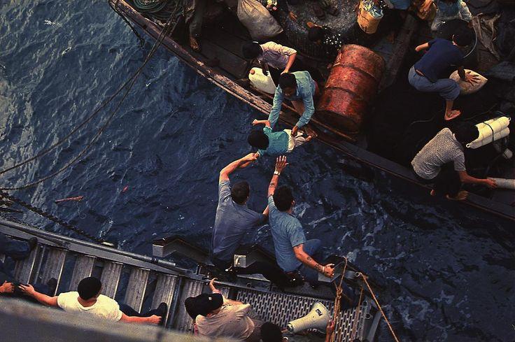 Vietnamese boat people fleeing communism climb climb aboard the USS Durham, 1975