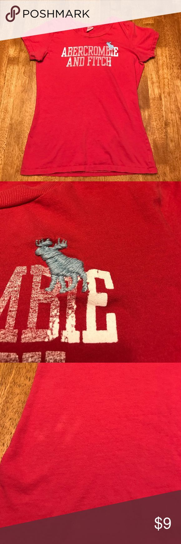 Abercrombie and Fitch T-shirt Red Abercrombie and Fitch t-shirt. Moose is embroidered and letters are screen printed.  Size is large but fits like a medium as this brand runs slim. There are two lightened/ discolored areas to bottom front of shirt per picture. As this brand often has a worn/aged look these marks may be original to design and not actual flaws. Abercrombie & Fitch Tops Tees - Short Sleeve