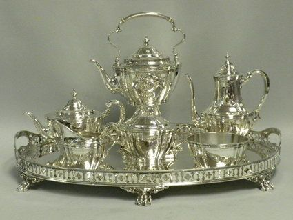 """This elegant 7 piece tea and coffee service by Tiffany & Co., New York, was made circa 1910 in the English Edwardian style. The set includes a coffeepot, teapot, kettle on stand with burner,l covered sugar bowl, creamer, waste bowl and a beautiful Tiffany & Co. paw footed pierced gallery tray in a complimentary style, circa 1905. The tea and coffee service is fully hallmarked with Tiffany & Co., makers, sterling silver 925/1000, """"m"""", and pattern #B16479."""