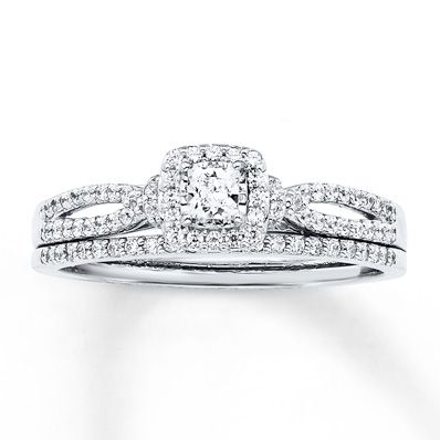 A princess-cut diamond outlined in sparkling round diamonds forms the center of her engagement ring in this lovely bridal set. Intertwining rows of round diamonds lend distinction to the 14K white gold band, while the matching wedding band features a row of additional round diamonds. The bridal set has a total diamond weight of 1/2 carat. Diamond Total Carat Weight may range from .45 - .57 carats.