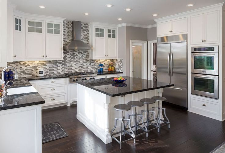 Traditional u shaped white cabinet kitchen with black countertops island and mosaic backsplash