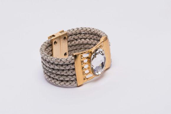 Bracelete em couro trançado branco gelo, base dourada com chaton cristal e atacador de imã dourado.    Tamanho: 17cm x 2,5cm