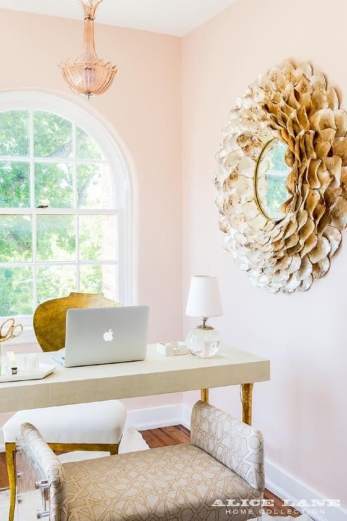 A gold shells mirror is mounted on pink walls painted in Farrow & Ball Pink Ground and reflecting cream colored desk finished with gold leaf twig legs flanked by a gold desk chair and a gray geometric bench on lucite legs located in front of a palladian window centered on the back wall behind the desk.