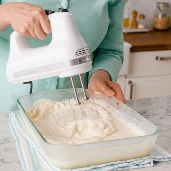 person using a hand mixture that has thickened on mixture in a glass 13x9 pan