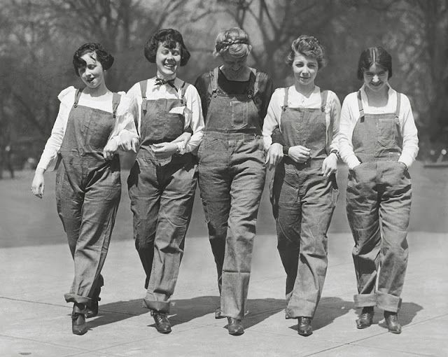 Five cheerful young women sporting overalls and boots [1920s]