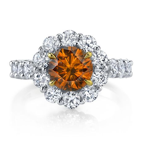 A 1.51 ct. GIA-certified fancy deep brownish yellow-orange brilliant cut diamond set in a halo setting of platinum and 18k yellow gold with 1.80 cts. t.w. colorless, VS round brilliant stones, and 0.07 ct. yellow stones
