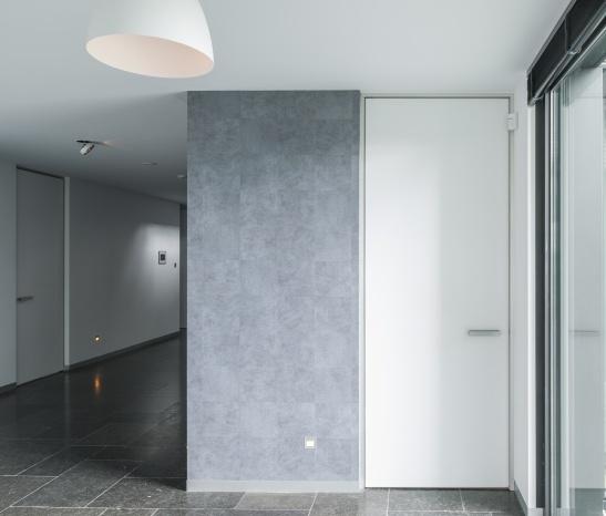 """In deze woning werd gekozen voor plafondhoge binnendeuren met een blokomlijsting. De deuren zijn ongeveer 2550mm hoog en 1000mm breed (op maat gemaakt). Qua grepen werd gekozen voor de kenmerkende vierkante DG.8 in geanodiseerd aluminium. De kleurkeuze """"D354-EM Designer White"""" komt zeer mooi tot haar recht in het modern vormgegeven interieur met donkere accenten in de vloer en op de wanden. www.anywaydoors.be"""