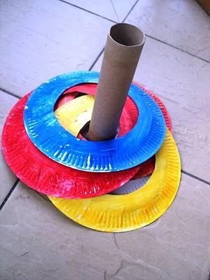 Rolo de papel toalha e pratos coloridos (ou pintados) de papelão cortados no centro.