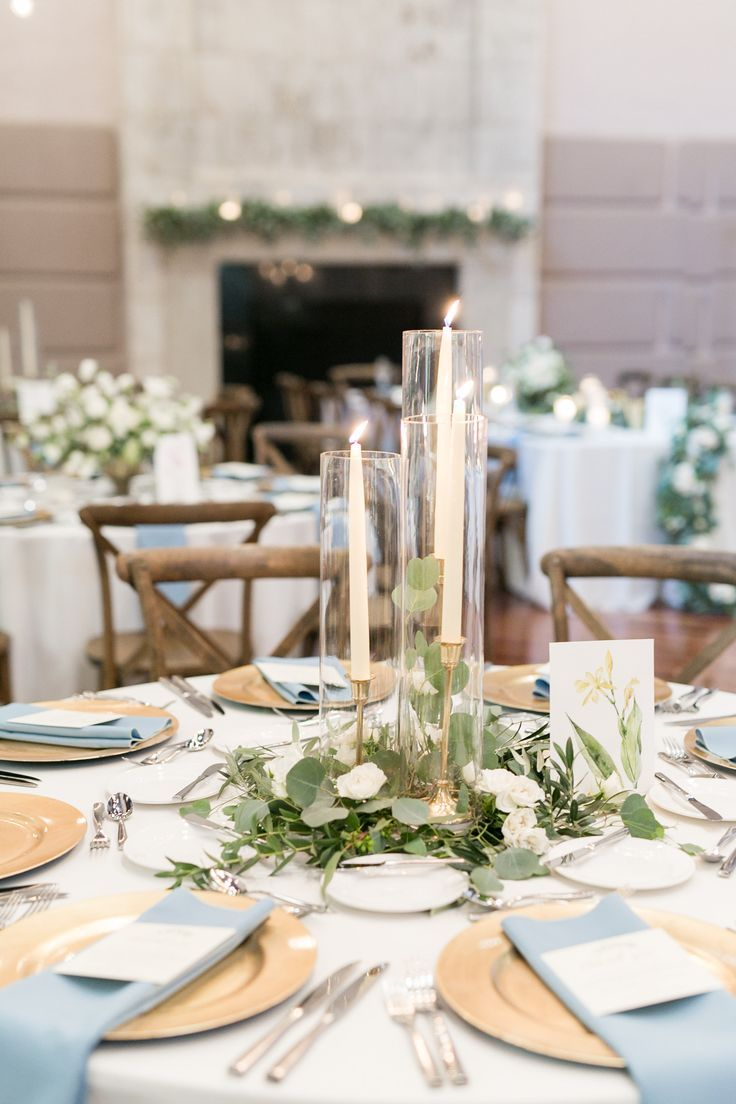 Elegant Simplicity In This Reception Centerpiece Of Eucalyptus And Olive Leaf Greenery Nestled Wi Round Wedding Tables Wedding Table Wedding Table Centerpieces