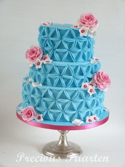 Blue and pink cake.  The design of this cake creates a triangle out a circle.  The pieces cover the entire cake.  Adorned with pink flowers.