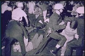 "August 26, 1968: Democratic National Convention Riots in Chicago: The police were taunted by the protesters with chants of ""Kill, kill, kill."" They sprayed demonstrators and bystanders indiscriminately with Mace. ... The entire event took place live under the T.V. lights for seventeen minutes with the crowd shouting, ""The whole world is watching."" http://en.wikipedia.org/wiki/1968_Democratic_National_Convention"
