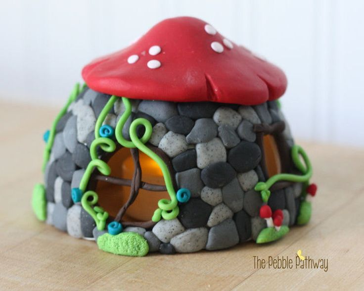 A whimsical fairy house to attract a fairy to your garden! This cute polymer clay fairy house looks like stone with a mushroom roof. There are windows that are open to catch a peak of your fairy inside.
