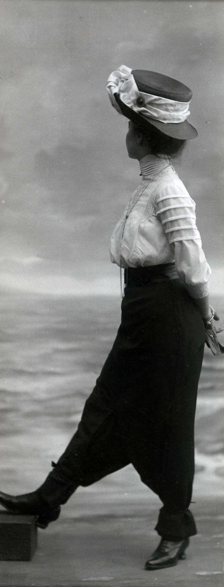 14-11-11  Damesmode. Model toont een broekrok met hoge taille en een mousseline blouse met hoge hals en een hoed. Zonder plaats, 1911.