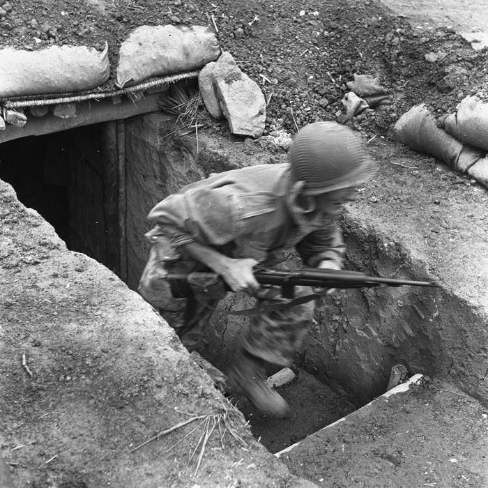 Pendant un tir d'artillerie du Viêt-minh, un sous-officier du 8e BPC (Bataillon de Parachutistes de Choc), armé d'une carabine américaine US M2, quitte précipitemment un abri pour rejoindre sa position de combat, lors de la bataille de Diên Biên Phu.