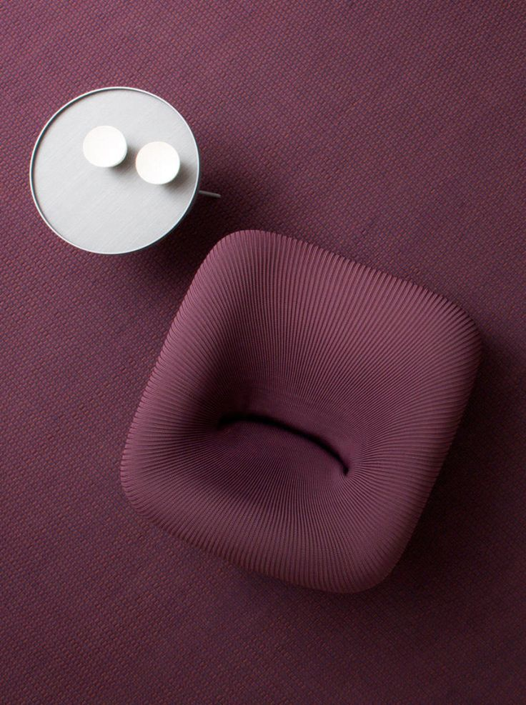 Textured Purple chair on purple rug with bright side table.