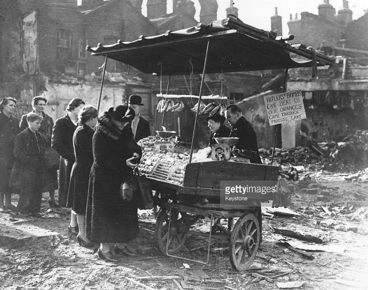 People queuing up at a fruit stall in bomb-damaged area of London.