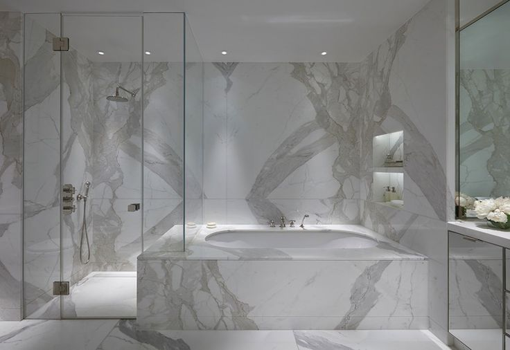 Absolutely stunning bathroom with glass walk-in shower filled with Statuario Marble tiles and shower floor next to Statuario Marble bathtub accented with marble niches.
