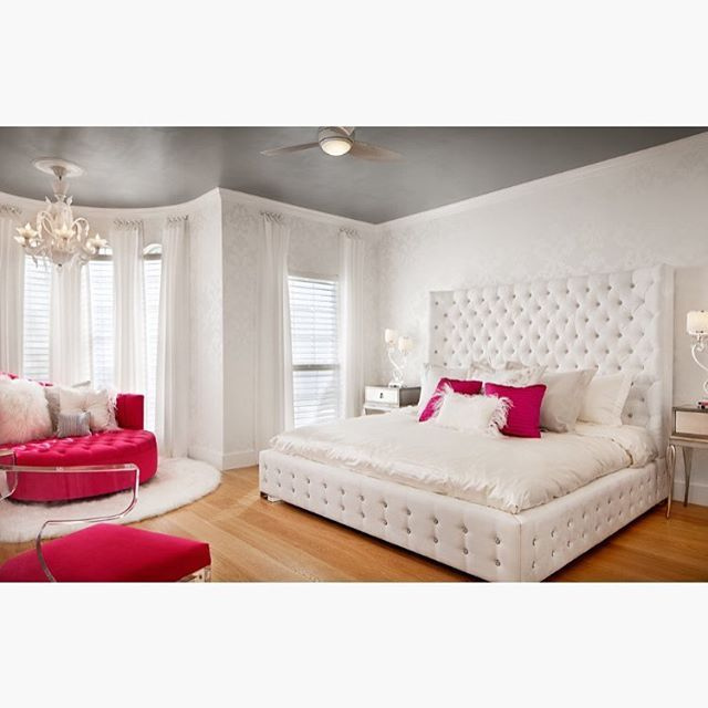 a tufted platform bed with a high headboard creates a luxurious atmosphere in this airy white bedroom hot pink accents a silver ceiling and an elegant